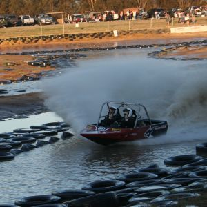 A V8 jet sprint boat races around the course.