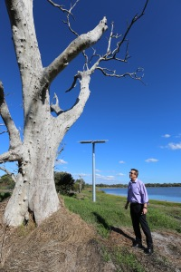 Mr Beaton stands in front of the raised solar panel that powers the pump floating atop the surface of the lake behind him.